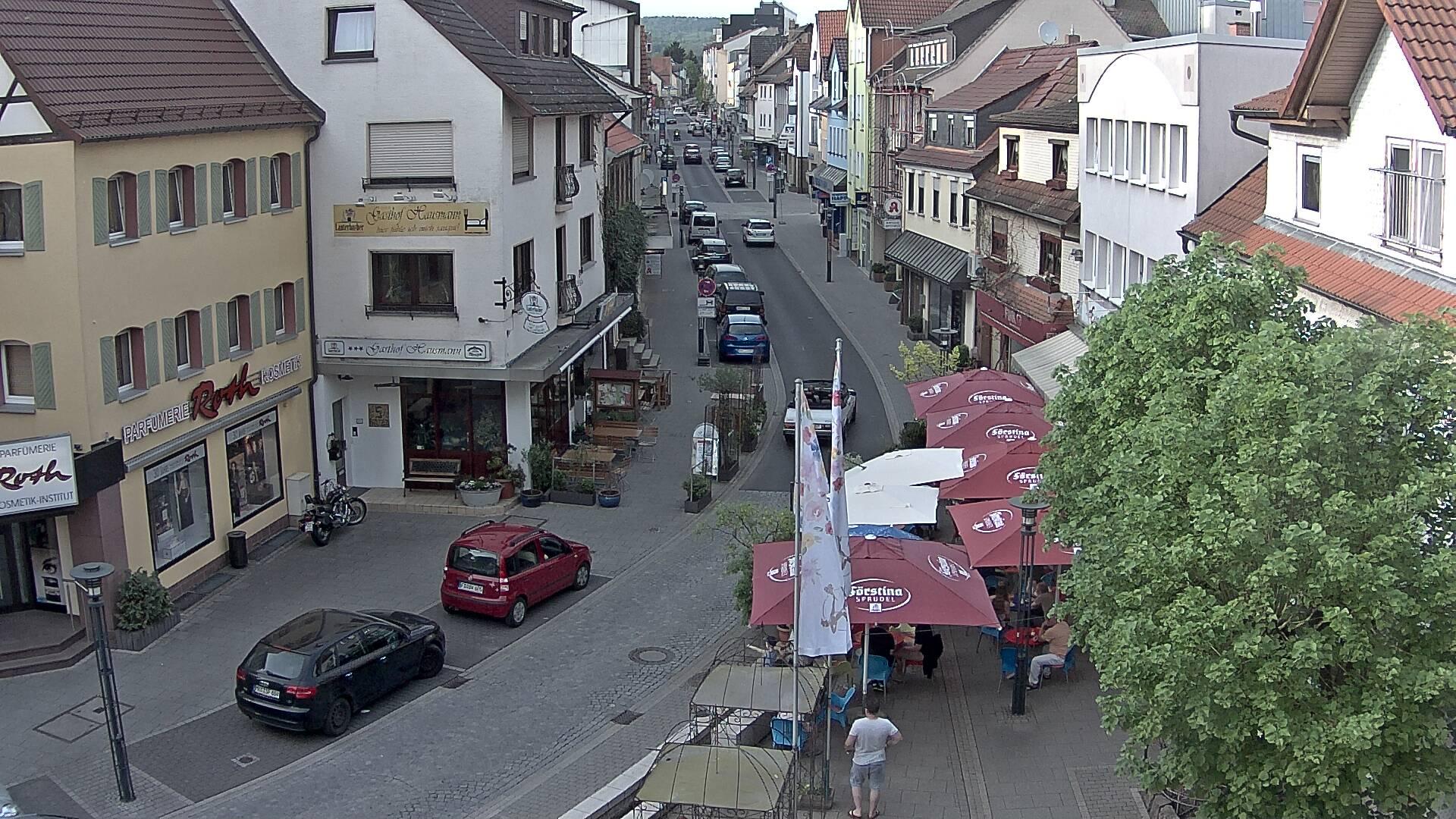 Blick von oben in eine belebte Straße mit breiten Gehwegen, rechts und links stehen Häuser. Vorn rechts ein Straßencafé mit Sonnenschirmen