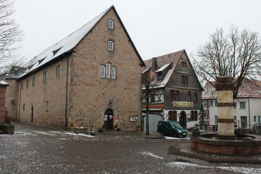 Blick auf einen menschenleeren Platz im Winter. In der Bildmitte die Giebelseiten von zwei historischen Gebäuden, rechts der Märchenbrunnen mit einer Säule.